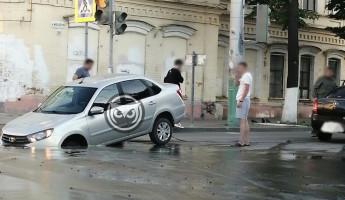 В центре города машина провалилась в яму с лужей